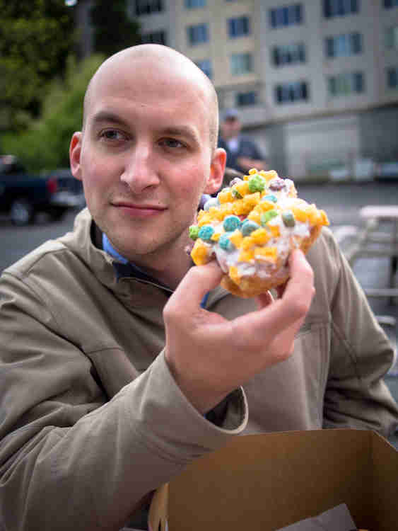 A VooDoo Doughnut covered in icing and Captain Crunch cereal