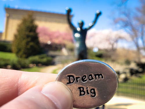 Dream Big coin in front of Rocky Balboa statue